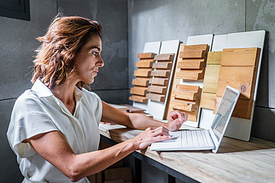 Woman working on laptop with wood tiles on desk at office - p300m2220608 by Javier De La Torre Sebastian