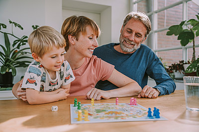 Parents playing board game with son looking away at home - p300m2226232 by Mareen Fischinger