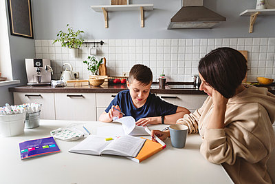 Mother assisting son in homework while sitting at dining table in kitchen at home - p300m2276718 by Katharina und Ekaterina