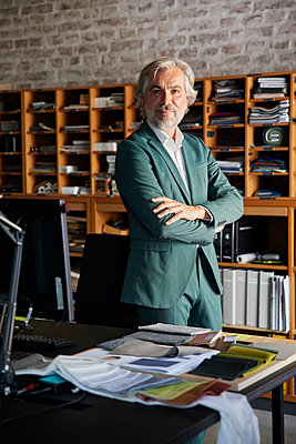 Mature male design professional standing with arms crossed by desk in office - p300m2300425 by Rainer Berg