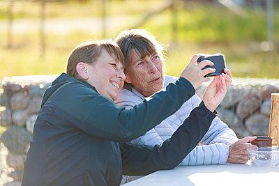 Smiling women taking selfie - p312m2237433 by Phia Bergdahl