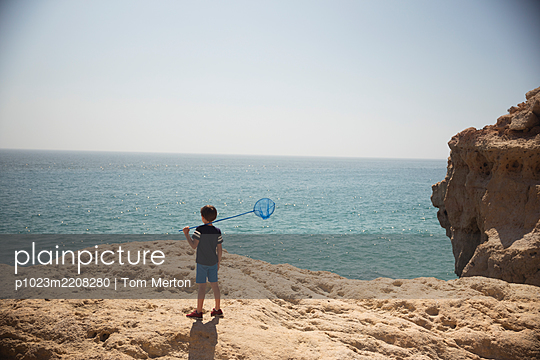 Boy with fishing net on rocks at sunny ocean - p1023m2208280 by Tom Merton