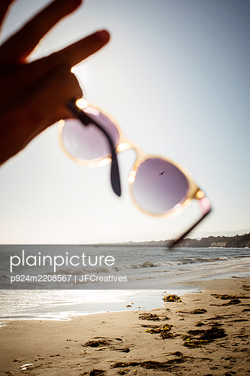 Close up of person on sandy beach, holding sunglasses towards the sun. - p924m2208567 by JFCreatives