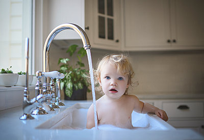 Portrait of cute shirtless girl bathing in sink at home - p1166m2033910 by Cavan Images