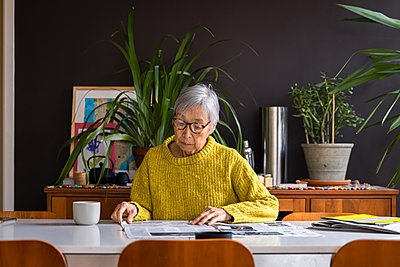 Senior woman wearing yellow sweater reading newspaper while sitting at dining table - p1166m2285610 by Cavan Images