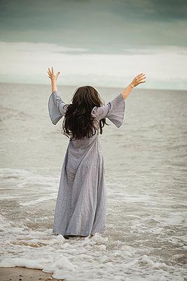 Frau mit langen dunklen Haaren und langem Kleid am Meer - p1628m2223332 von Lorraine Fitch