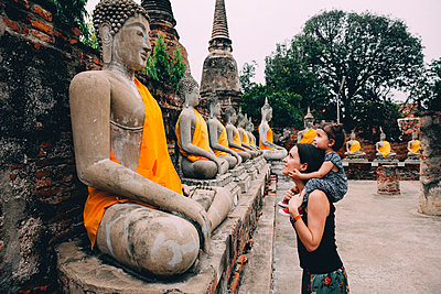 Thailand, Bangkok, Ayutthaya, Buddha statues in a row in Wat Yai Chai Mongkhon, mother and daughter in front of a buddha statue - p300m1587335 von Gemma Ferrando