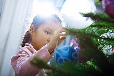 Little girl decorating Christmas tree - p300m2023810 von Arman Zhenikeyev