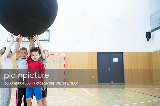 Pupils holding big ball in gym class - p300m2004358 von Fotoagentur WESTEND61