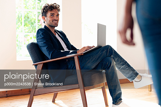 Smiling businessman looking at woman while working on laptop at home - p300m2243538 by Steve Brookland