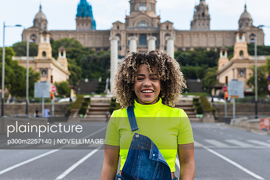 Cheerful woman standing on street against buildings in city - p300m2257140 by NOVELLIMAGE