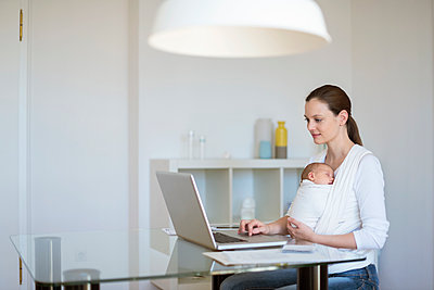Mother with baby girl in sling working from home - p300m1228345 by Daniel Ingold
