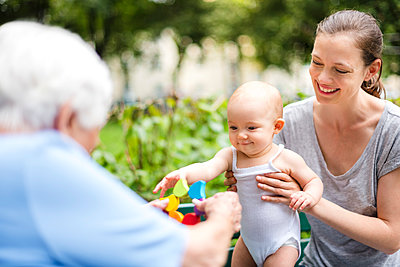 Portrait of smiling baby girl with grandmother and mother in a park - p300m1549544 by Daniel Ingold