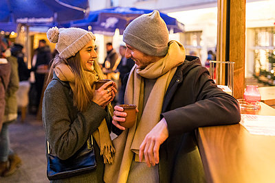 Happy young couple drinking mulled wine at Christmas market - p300m1588110 by William Perugini