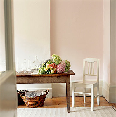 Dining room with large wooden table and a bouquet of fresh flowers - p349m695116 by Emma Lee
