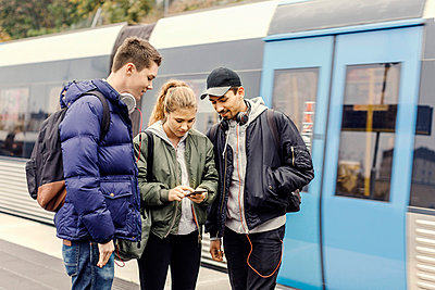 Multi ethnic university students using mobile phone at subway station - p426m1003753f by Maskot