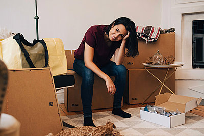 Portrait of smiling woman sitting on cardboard box at home - p426m1542787 by Maskot