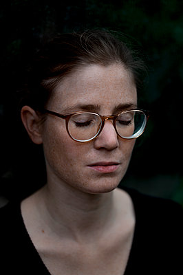 Woman with glasses, eyes closed, portrait - p552m2164138 by Leander Hopf