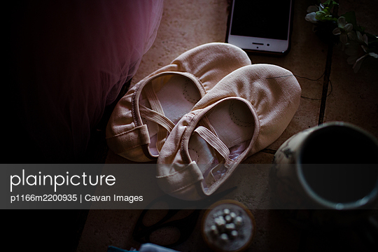 Ballet shoes sitting on table - p1166m2200935 by Cavan Images
