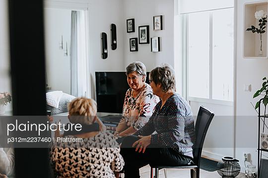 Senior friends talking together at home - p312m2237460 by Plattform