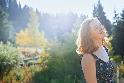 Portrait carefree young woman in sunny park - p1023m2088004 by Arman Zhenikeyev