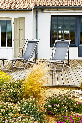 Blooming flowers on a terrace with loungers made of weathered wood at a country home - p1183m997157 by Bouchet, Guy