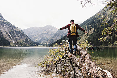 Austria, Tyrol, Alps, hiker balancing on tree trunk at mountain lake - p300m1505591 by Uwe Umstätter