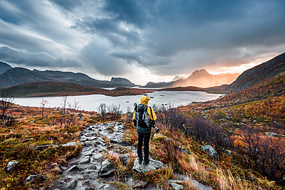 Norway, Lofoten Islands, Hiker on the way to Kvalvika Beach - p300m2104622 by Valentin Weinhäupl