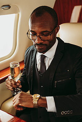 Male entrepreneur holding champagne while checking time on wristwatch in private jet - p300m2256406 by OneInchPunch