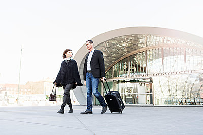 Full length of business people with luggage walking outside railroad station against clear sky - p426m1085318f by Kentaroo Tryman
