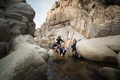 Children playing on rocks in river, Lake Arrowhead, California, USA - p924m1557699 by JLPH