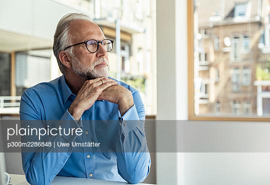Businessman wearing eyeglasses while contemplating at desk - p300m2286848 by Uwe Umstätter