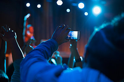 Crowd photographing DJ on stage in nightclub - p1192m1016429f by Hero Images