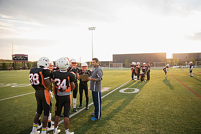 Coach with clipboard talking to teenage boy high school football team on football field - p1192m1500250 by Hero Images