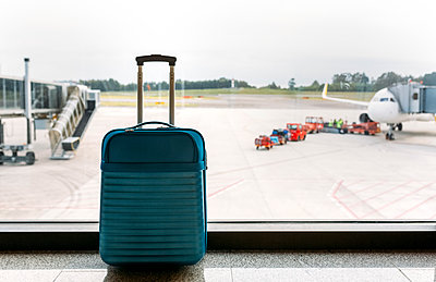 Suitcase at the airport, passenger airplane and luggage vehicle in the background - p300m1153483 by Marco Govel