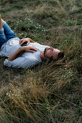 Relaxed man lying in field listening to music with headphones - p300m2042008 von harrylidy