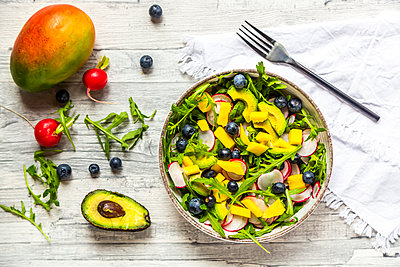 Bowl of rocket salad with mango, avocado, red radishes and blueberries - p300m2103597 von Sandra Roesch