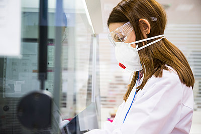 Young woman wearing safety mask and goggles while working in a laboratory - p300m2143334 by Andrés Benitez