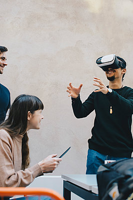 Smiling male computer programmer gesturing while using VR glasses by colleagues in office - p426m1494001 by Maskot