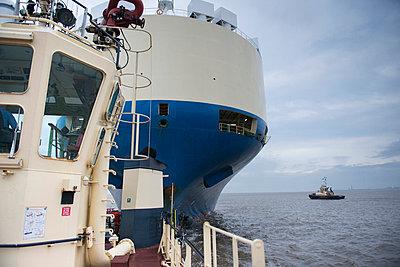 Tugboat towing ship to harbor - p429m747078f by Monty Rakusen