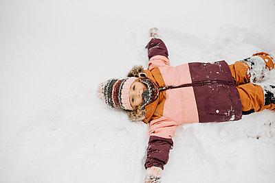 Canada, Ontario, Girl (2-3) doing snow angels - p924m2271208 by Sara Monika