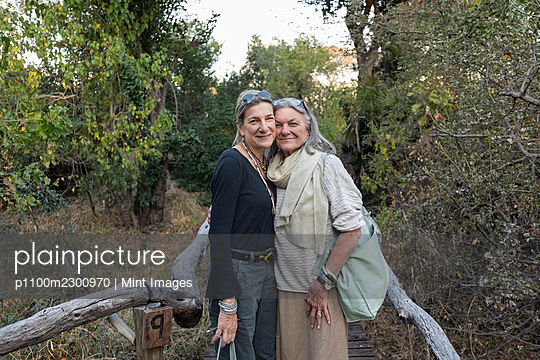 An adult woman and her mother on a walkway through the trees at a safari camp - p1100m2300970 by Mint Images