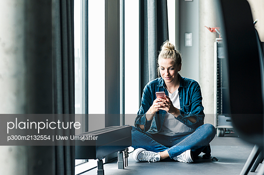 Businesswoman sitting on the floor in office using cell phone - p300m2132554 by Uwe Umstätter