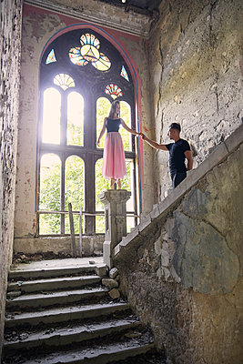 Ballerina standing on newel post while holding male friend's hand in old building - p1166m2024707 by Cavan Images