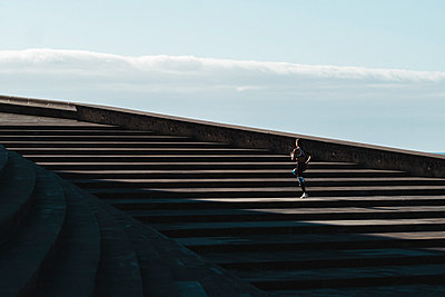 Pulled back of woman running on stairs with blue sky in background - p1166m2136140 by Cavan Images
