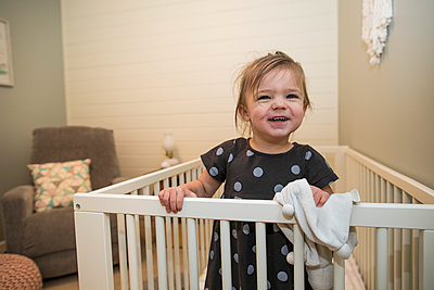 Portrait of cute toddler girl in her crib in bedroom. - p1166m2163006 by Cavan Images