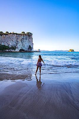 Frau steht vor einer Felslandschaft am Meer - p1455m2203714 von Ingmar Wein