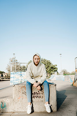 Teenage girl in hooded shirt sitting on concrete wall - p1628m2210756 by Lorraine Fitch
