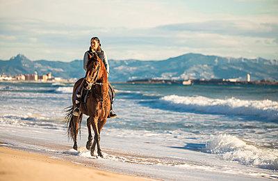 Spain, Tarifa, woman riding horse on the beach - p300m2080671 by Sebastian Kanzler