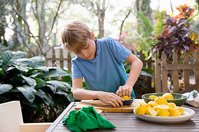 Boy squeezing lemon for lemonade at garden table - p924m1446874 by Kinzie Riehm